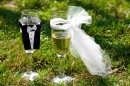 two glasses of champagne in the clothes of bride and groom standing on the grass